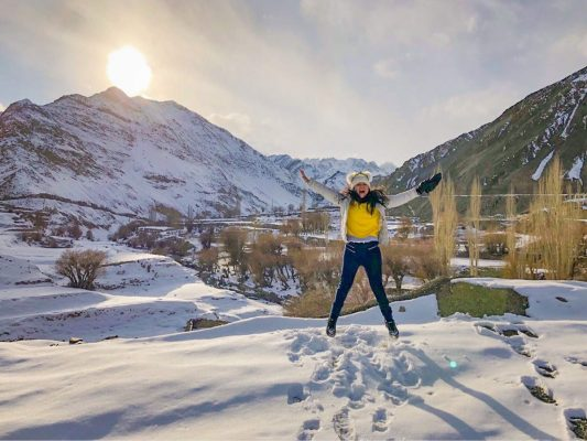 A picture on a woman jumping on snow, sun shining behind, mountain range